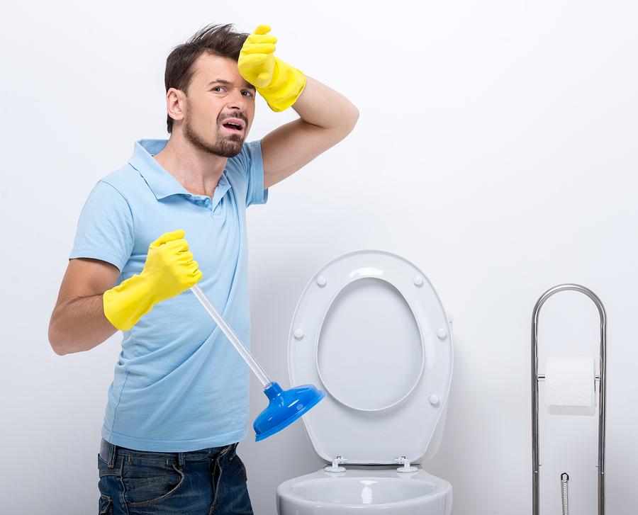 Plumber working on overflowing toilet