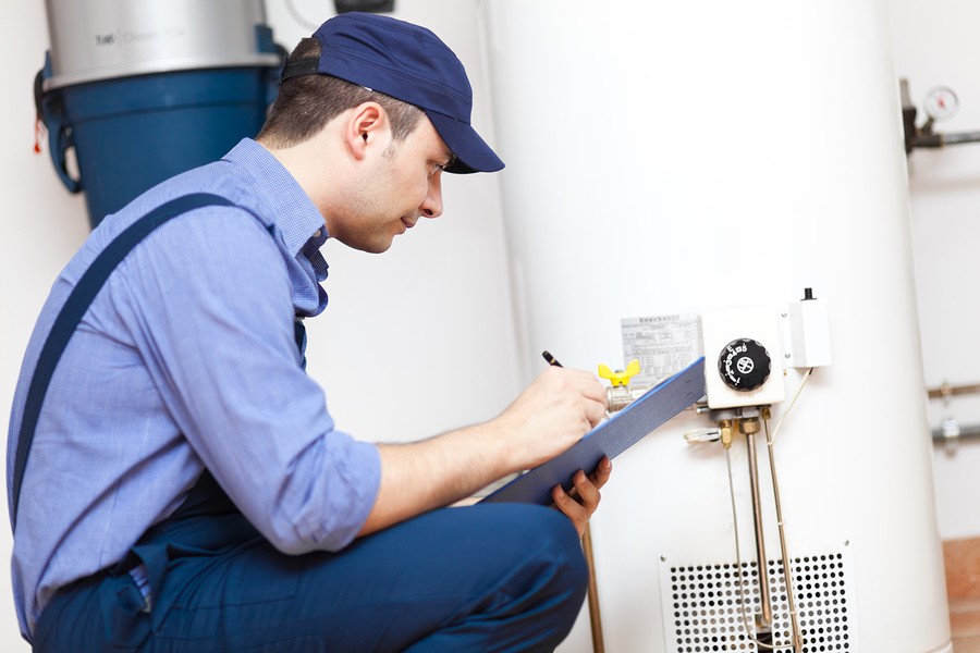 A plumber repairing a leaking water heater