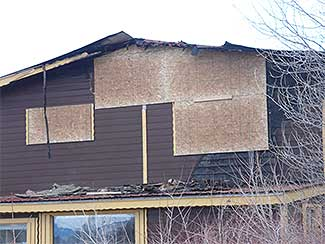 Damaged home requiring board up services.