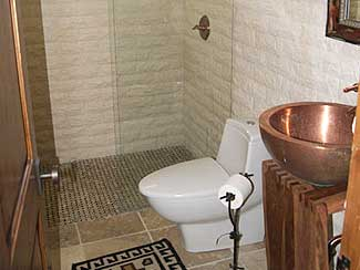 Bathroom with copper sink, and glass shower.