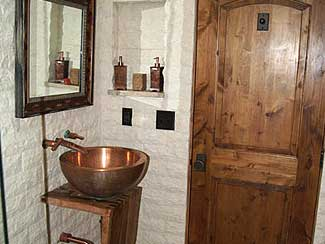 Bathroom with copper sink and dark wooden door.